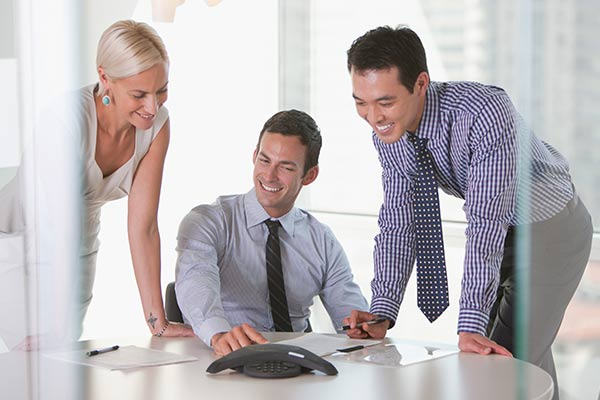 A woman and two men happily sitting on a conference call